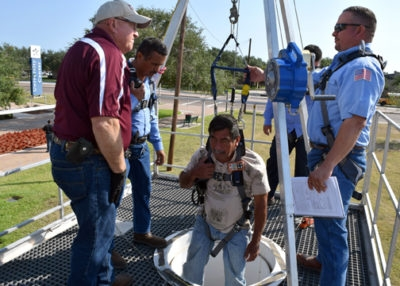 Marco Salinas from the Brownsville Public Utilities Board hangs from a harness and is hoisted down a makeshift manhole during confined space training at the Infrastructure and Safety Summit recently hosted at Texas State Technical College (photo TSTC)