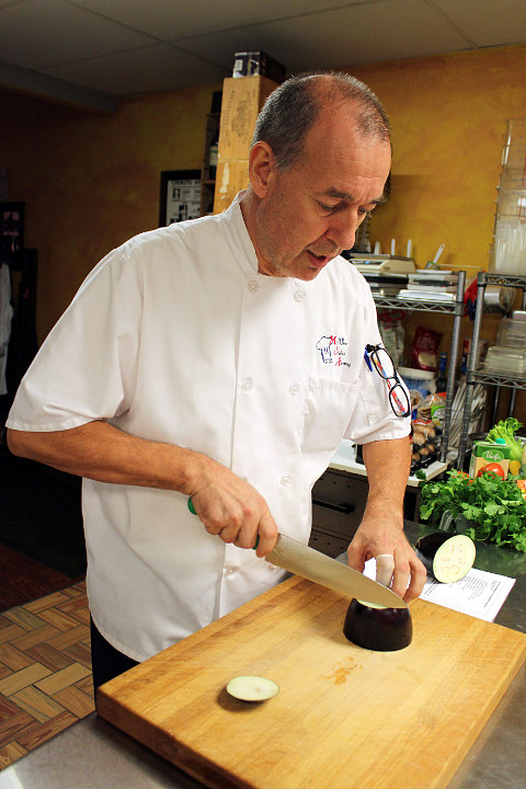 Chef Marcel demonstrates how to slice an eggplant at the start of a lesson on vegetarian cooking. (VBR)