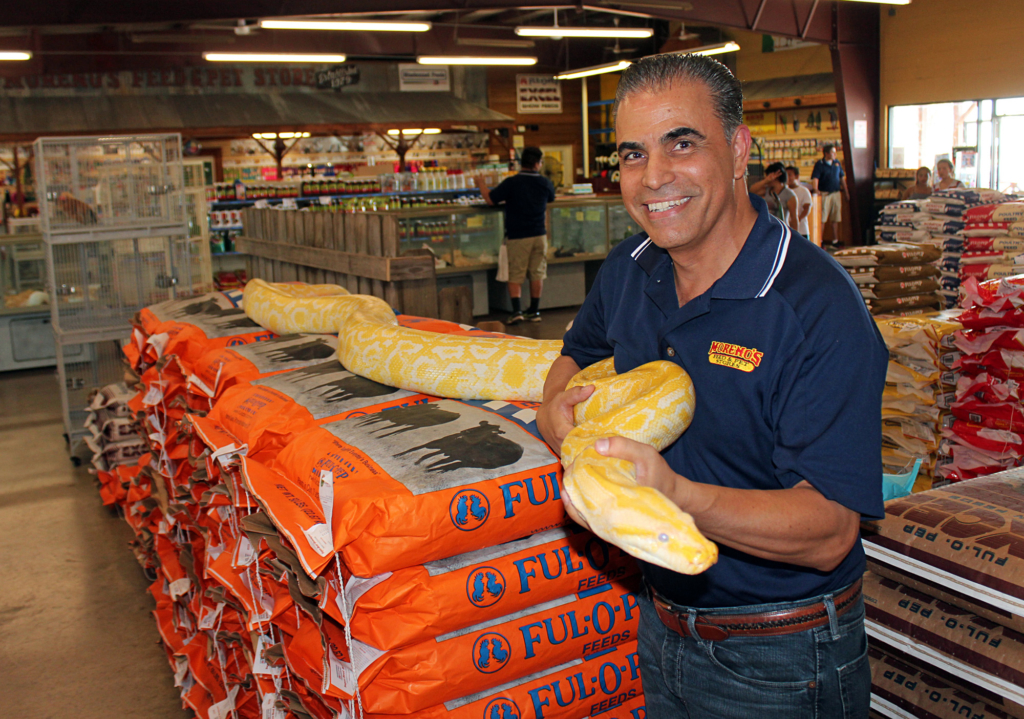 Owner Leroy Moreno with one of his personal pets, an albino Burmese python. (VBR)