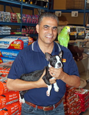 Owner Leroy Moreno shows off two of his animals, a parrot and a boxer puppy. (VBR)
