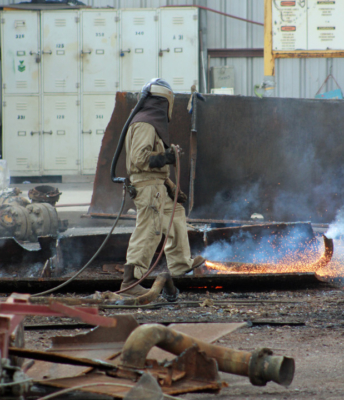 A worker at International Shipbreaking uses a special apparatus that pumps filtered and cooled air into his helmet as he uses a torch to cut up a piece of the USS Ranger. (VBR)