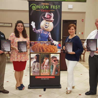 Texas Onion Fest Committee Chair Daryl Smith, Weslaco Chamber Marketing Director Laura Espinoza, Liz Gonzalez and Weslaco Chamber President/CEO Doug Croft display the festival's awards from TFEA. (photo Weslaco Chamber)