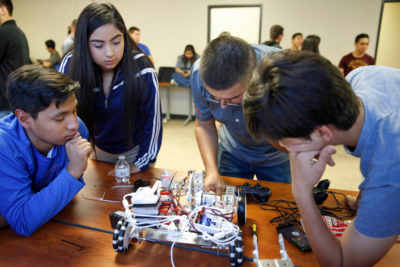 Students perform repairs and modifications on a robot. (photo Paul Chouy, UTRGV)