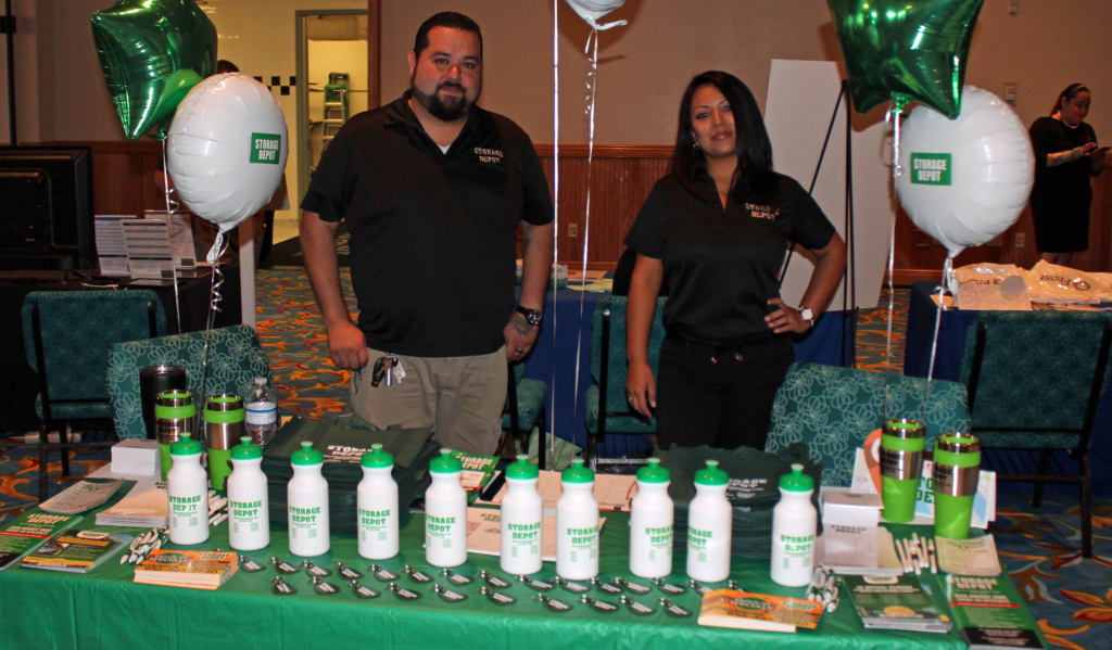 Some booths, like this one for Storage Depo, were colorfully decorated and offered giveaways for visitors. Pictured are Flor Herrera and Jonah Canales.