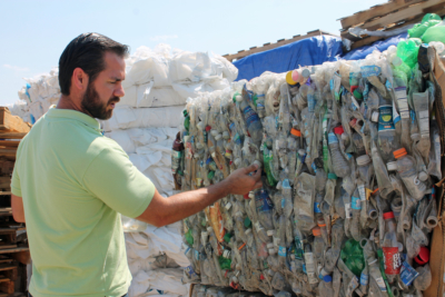 Ruben Geurrero Jr. inspects a bale of plastic bottles before it is shipped out for recycling.