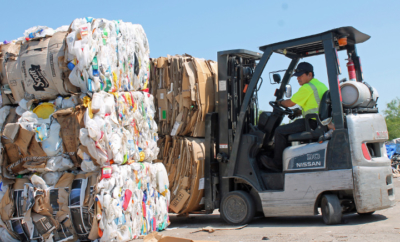 A forklift driver moves bales of cardboard ready for recycling.