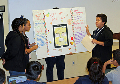 Three students present their concept for a mobile app that would scan the contents of an individual's refrigerator and pantry and find recipes to use those ingredients.