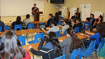 Computer science teacher Daniel Reyna talks to his students.