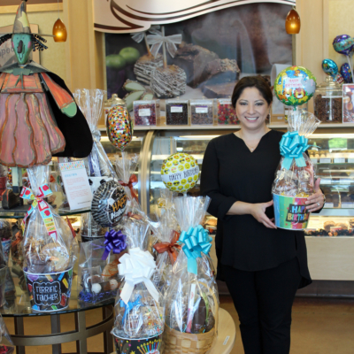 Veronica Barrera-Cuellar with gift baskets prepared by Rocky Mountain Chocolate Factory for special occasions. (VBR)