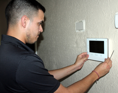 Smith Security technician Alvin Lopez installs a security system control panel at a Weslaco business. (VBR)