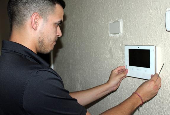 Smith Security technician Alvin Lopez installs a security system control panel at a Weslaco business. (VBR)
