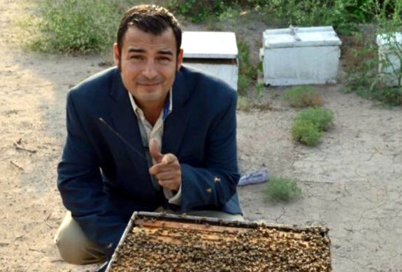 Bee Strong Honey owner Luis Slayton with a bee hive.