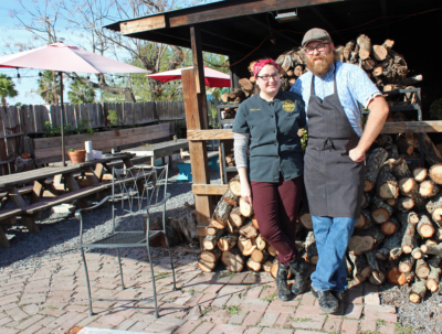 Rio Grande Grill owners Stephania and Daniel Wright with mesquite and pecan wood used for smoking meats.