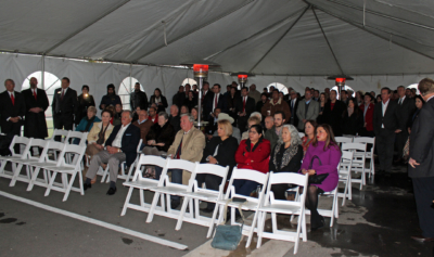 Business leaders gathered under a tent for shelter from the cold and rain at the groundbreaking.