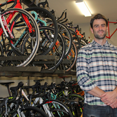 7th and Park owner Graham Sevier-Schultz with a selection of new and used bicycles.