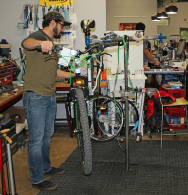 Mechanic Jorge Guerrero works on a bicycle in the shop area.