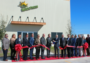 Index Fresh Board Chairman John Grether and President and CEO Dana Thomas (holding scissors) prepare to cut the ribbon on the company's 60,000-square-foot avocado packing and ripening facility in Pharr.
