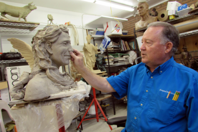 Sculptor Doug Clark shapes clay on a work in progress at his studio.  (VBR)