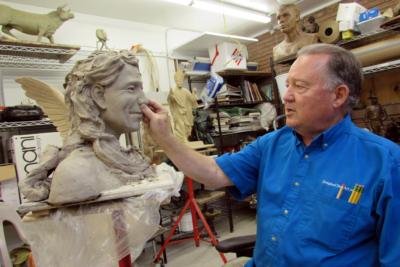 Sculptor Doug Clark shapes clay on a work in progress at his studio.  (VBR)