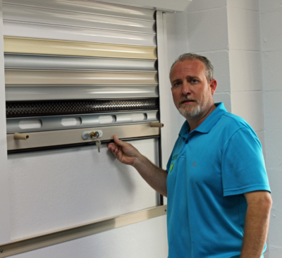 Owner Jeremy Holden with a manually operated shutter often used by businesses for security. (VBR)