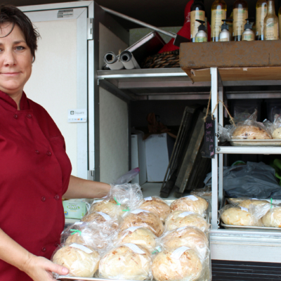 Peggy Harris with some of her gluten-free breads at a farmers market. (VBR)