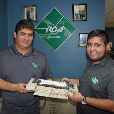 Jose David Avila and his son David hold a vintage IBM keyboard like one they sold online for $1,000. (VBR)