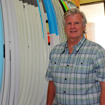 Island Native Surf Shop owner Kerry Schwartz stands among some of the surfboards he sells. (VBR)