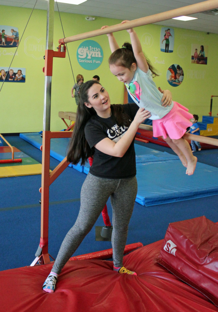 An instructor helps a young girl learn to swing on the parallel bars. (VBR)