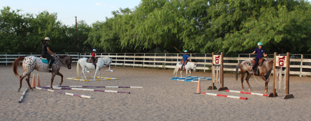 A group of young riders navigate a series of obstacles in the training arena at JHK Equestrian Country Club. (VBR)
