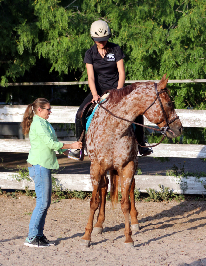 JHK Equestrian Country Club owner Jamie Ricks helps a young rider adjust her stirrups before class. (VBR)