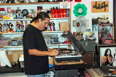 Valley Vinyls owner Victor Cantu spins an album on the turntable of his store's sound system. (VBR)