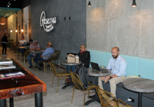 Customers visit or work on laptops while sampling coffee from different parts of the world. (VBR)