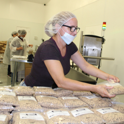 Romi Cordova, a veteran worker at Dipasa, arranges bags of roasted sesame seeds. (VBR)