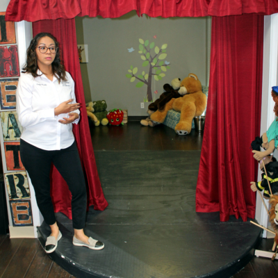 Cindy Perez-Waddle, a licensed professional counselor, stands on the stage of a mini-theater where children can use puppets and other props to act out their feelings. (VBR)