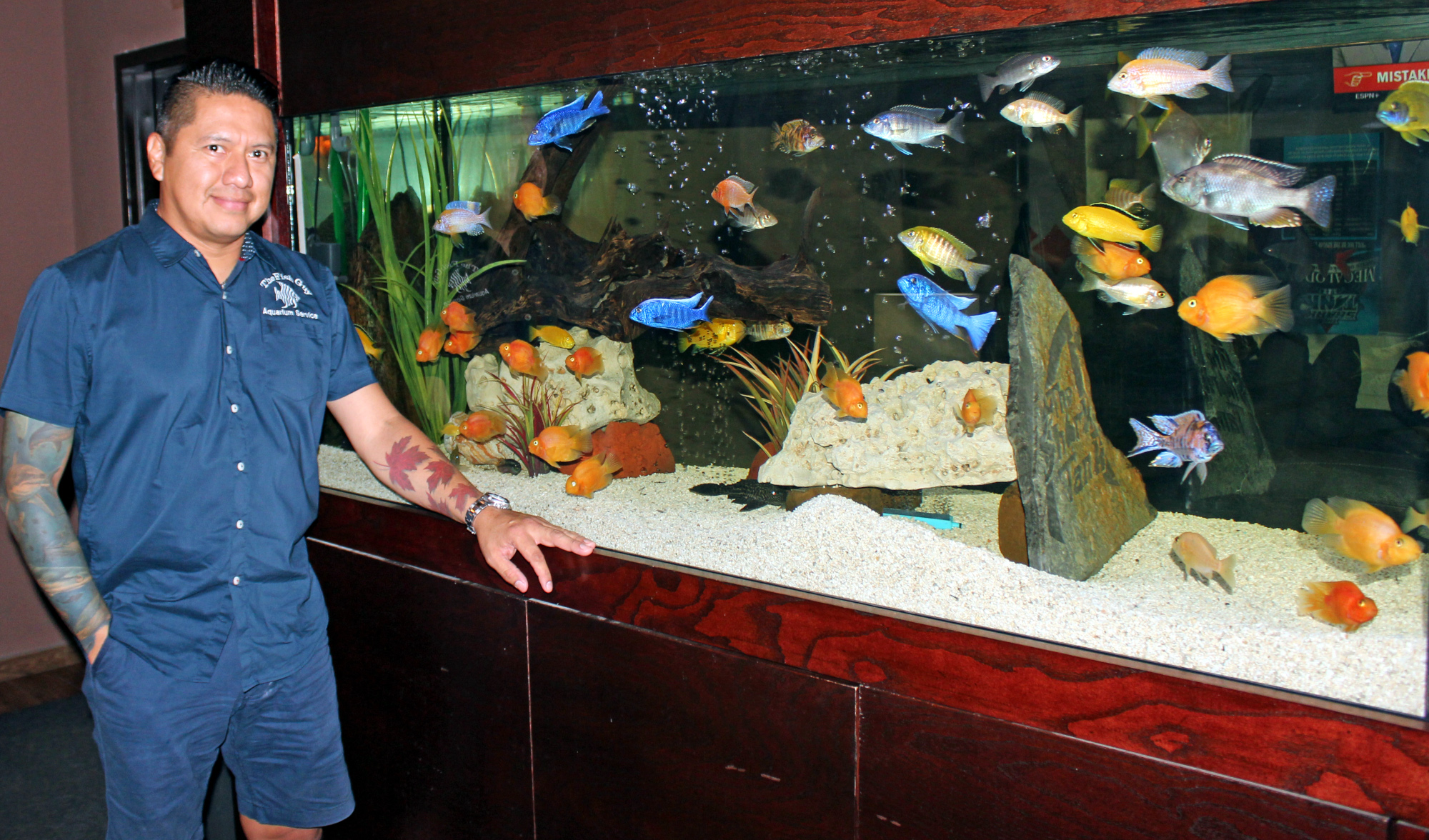Isaac Ramirez, known as The Fish Guy, with a saltwater aquarium he designed and installed in a business in Edinburg. (VBR)