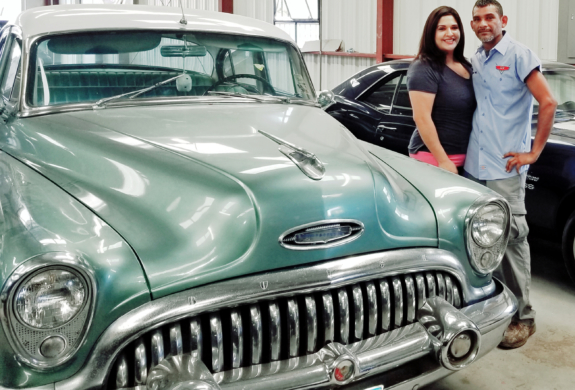 SS Auto Body Solutions owners Rachel Hinojosa and Rene Moreno next to a classic car in their shop. (VBR)