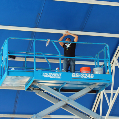 A Tenzo employee cleans a large shade structure prior to the new school year at Covenant Christian Academy in McAllen. (VBR)