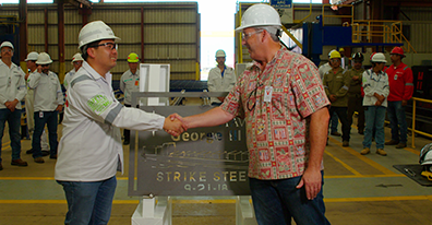 Keppel AmFELS president Simon Lee, left, shakes hands with George Pasha, IV, president of The Pasha Group, during the cutting of the first steel plates for the M/V George III, one of two containerships the Brownsville-based company will build.
