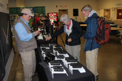 A pair of visiting birdwatchers check out the latest binoculars and spotting scopes at the RGV Birding Festival. (VBR)