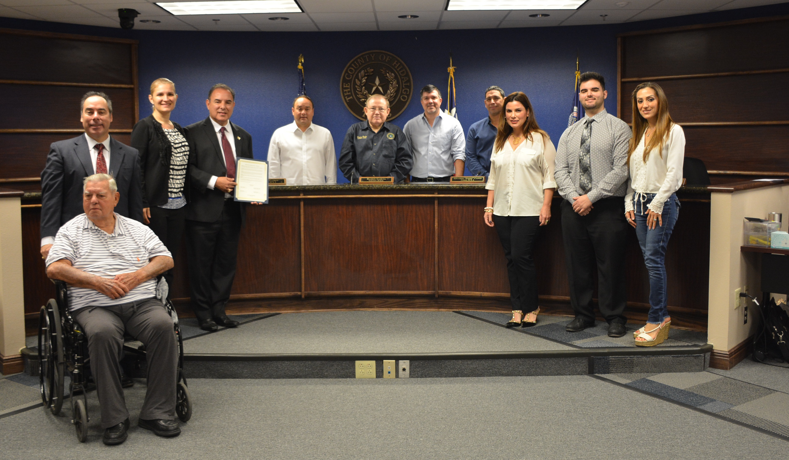 Dr. Jose L. Cazares Jr. holds up the proclamation of Dentist of the Year with Commissioners Court and his family. (courtesy)