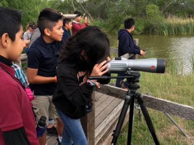 Schoolchildren on a field trip to Estero Llano Grande use a spotting scope to view wildlife. (Copyright TPWD)