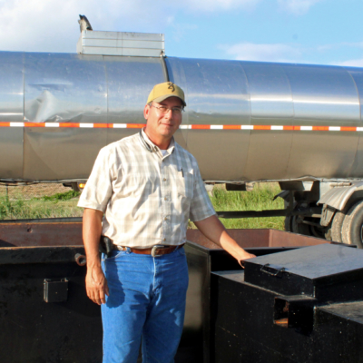 Fatty Chem plant manager Hector Martinez stand in front of a company tanker truck and next to used cooking oil collection containers. (VBR)