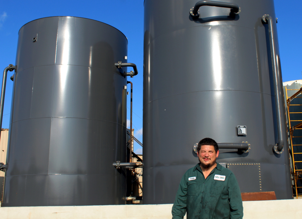 Chem employee Freddy Villanueva stands in front of large tanks used to process used cooking oil. (VBR)