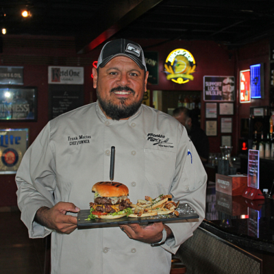 Owner and chef Frank Macias with the Trump's Burger Wall, piled high with American and Mexican flavors representing the cultural mix of South Texas. (VBR)