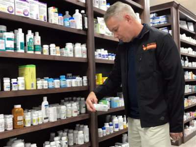 Pharmacist John Hinkle checks a drug label at the new Mid-Valley Pharmacy in Mercedes. (VBR)