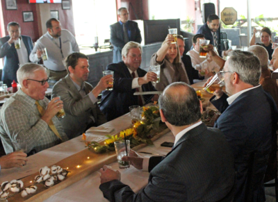 Harlingen Mayor Chris Boswell (center) lifts a glass with others to toast American Airlines official Dale Morris.