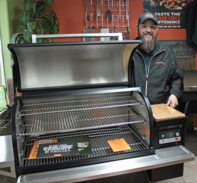 South Texas Outdoor Kitchens owner Rick Cardenas with a gas grill that uses wood pellets to infuse a smoky flavor into meats. (VBR)