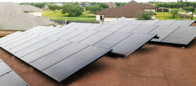 A solar panel installation on a flat roof in a residential neighborhood is not visible from the ground. (Courtesy)