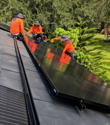 Workers install a solar panel array on the roof of a residence. (Courtesy)