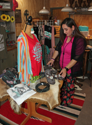 Crissy Santana arranges merchandise in the Bootique's newly created western wear section. (VBR)